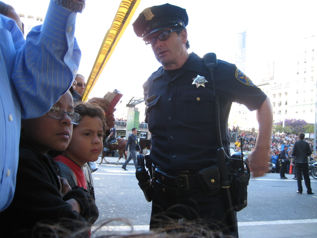 A San Francisco police officer chats with young Isaiah and  Manuel as they wait outside Macy's for a glimpse of Batkid. PHOTO BY MELISSA MCROBBIE
